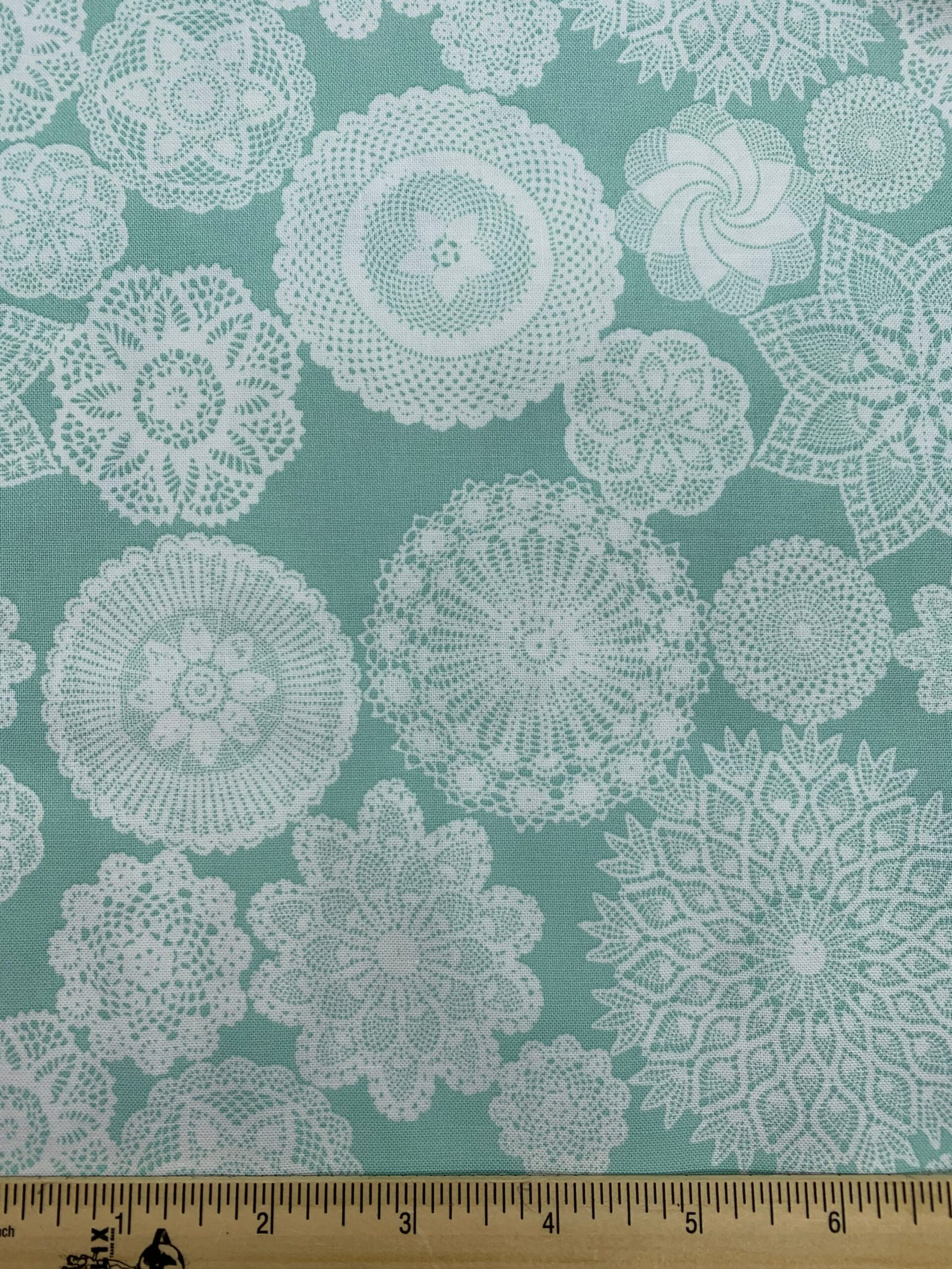 White doilies on an aqua background quilting fabric