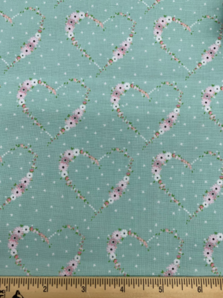 Pale pink flowers in the shape of a heart on a pale aqua background quilting fabric