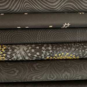 A pile of black quilting fabrics