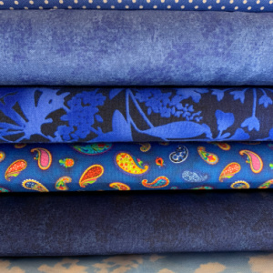 A pile of blue quilting fabrics