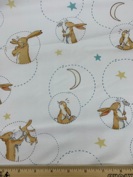 Nut Brown Hare with flower on White Quilting Fabric by Sam McBratney from Guess How Much I Love You for Clothworks