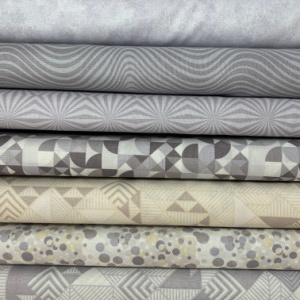 A pile of grey quilting fabrics