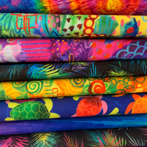 A pile of multi coloured quilting fabrics