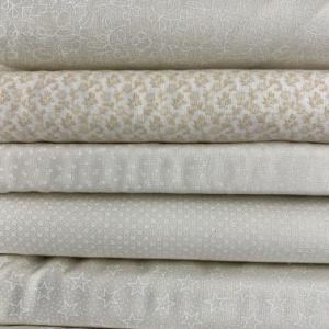 A pile of cream quilting fabrics