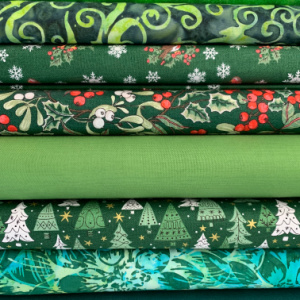 A pile of green quilting fabrics