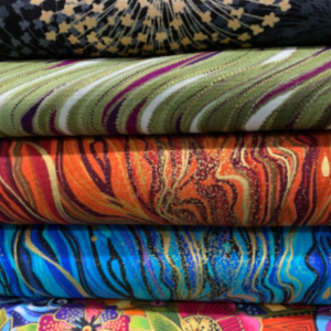 A pile of metalic quilting fabrics
