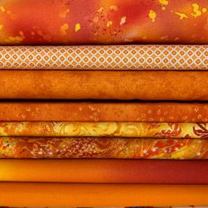 A pile of orange quilting fabrics