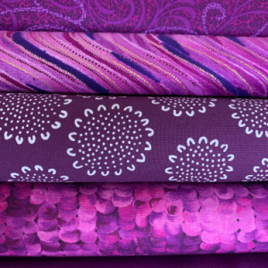 A pile of purple quilting fabrics