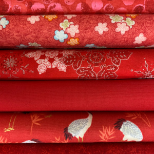 A pile of red quilting fabrics
